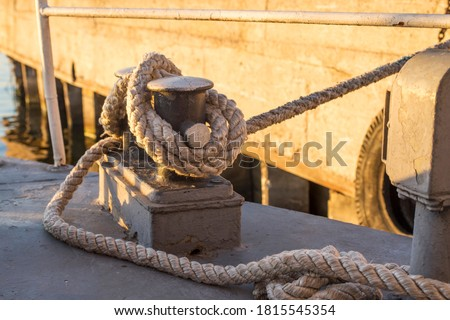 Tied rope knot on metallic bollard , seafaring port. Nautical ship moored in dock. Anchor rope in the port, ship mooring tool. Royalty-Free Stock Photo #1815545354