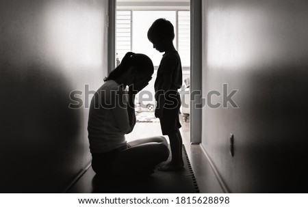 Mother crying next to her child. Family divorce, death and hardship concept.  #1815628898