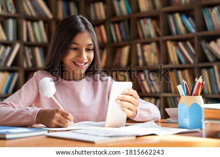 Indian latin child preteen school girl holding phone distance learning class using mobile application, watching online lesson, video calling in app making notes studying at home, in classroom. #1815662243