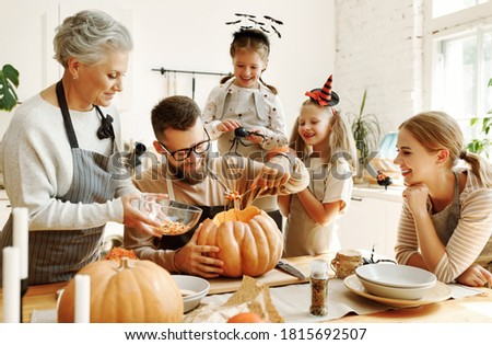 Happy multi generational family smiling and carving jack o lantern from pumpkin while gathering around table during Halloween celebration Royalty-Free Stock Photo #1815692507