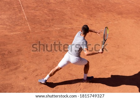 Professional tennis player performs forehand hit on clay tennis court. Young male athlete with tennis racket in action. Junior tennis sport. Back view, shadow, copy space Royalty-Free Stock Photo #1815749327