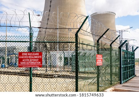 """Security fence of a nuclear power plant in France with barbed wire and warning signs reading """"Nuclear area with restricted access. Forbidden access without authorization"""". #1815749633"""