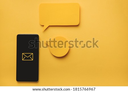Smartphone and Message bubbles chat papper on yellow background Royalty-Free Stock Photo #1815766967