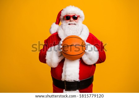 Portrait of his he nice attractive cheerful cheery sporty Santa holding in hands orange ball season team league isolated over bright vivid shine vibrant yellow color background