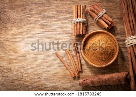 Cinnamon sticks and powder on a wooden table, top view Royalty-Free Stock Photo #1815783245