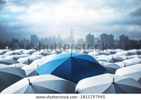 Blue umbrella on top of other gray umbrellas on city background. Business and safety concept #1815797945