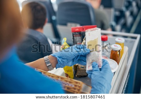 Back view focused image of table with snack and drinks while female air hostess serving meal for the passenger of first class #1815807461