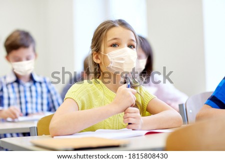 education, school and pandemic concept - student girl wearing face protective medical mask for protection from virus disease with group of classmates on lesson at classroom Royalty-Free Stock Photo #1815808430