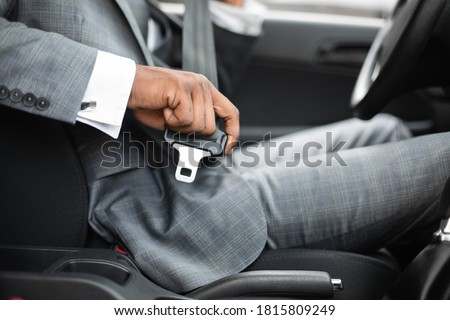 Driving safety concept. Unrecognizable black businessman fasten seat belt in his car, ready to go to office. African american man in stylish suit putting on his seatbelt before driving car, cropped Royalty-Free Stock Photo #1815809249