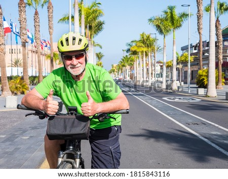 Senior man with glasses and yellow helmet riding  his bicycle in the deserted road Tenerife, Canary islands. No tourism due to Covid-19 coronavirus. Palm trees and blue sky in background Royalty-Free Stock Photo #1815843116