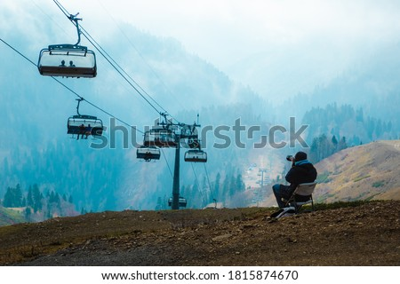 Photographer taking pictures of people sitting in the cabin of the cable car against the background of blue mountains in the fog