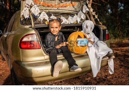 Alternative safe celebration. Cute kids celebrating Halloween party in the trunk of car with spider net, ghosts, carved pumpkin in medical mask for fun and other decoration, autumn outdoor Royalty-Free Stock Photo #1815910931
