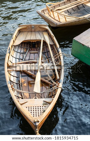 wooden boat with oars at the pier Royalty-Free Stock Photo #1815934715