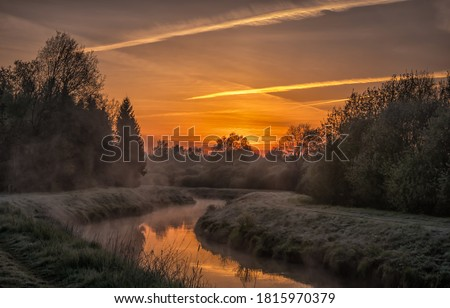 Sunrise rural river fog landscape. Morning sunrise fog over rural river. Rural river sunrise fog landscape. Sunrise fog landscape Royalty-Free Stock Photo #1815970379