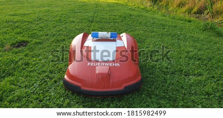 A rebuilt fire department lawnmower robot at work taking pictures from the front in a green meadow Translation : fire department