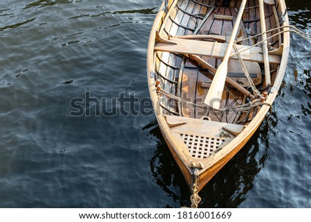 bow of a wooden boat with oars Royalty-Free Stock Photo #1816001669