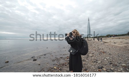 Woman takes photos on camera of sea in cloudy weather. Action. Professional photographer woman takes pictures of sea standing on background of cloudy sky