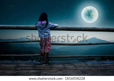 The little girl stood at a mountain viewpoint looking at the full moon in the lonely night.