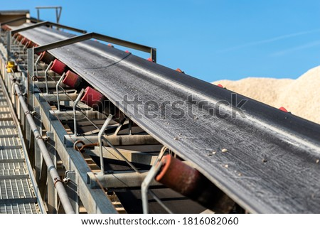 Close-up shot of the conveyor belt in the concrete plant with transport rollers, visible metal stairs. Royalty-Free Stock Photo #1816082060
