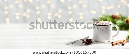 Christmas banner with white cup with hot chocolate and marshmallows on with cinnamon sticks and fir xmas tree branches with beautiful garland lights. New year celebration #1816157330