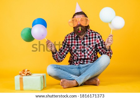 fun and happiness concept. happy man holding colorful helium balloons. hipster smiling happily. having fun on party. prepare for holidays. Event manager poses with festive accessory.
