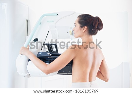 Young woman at breast cancer prevention screening at hospital. Hardware examination of the breast. Healthy young woman doing cancer prophylactic mammography scan. Modern hospital with hi-tech machine #1816195769
