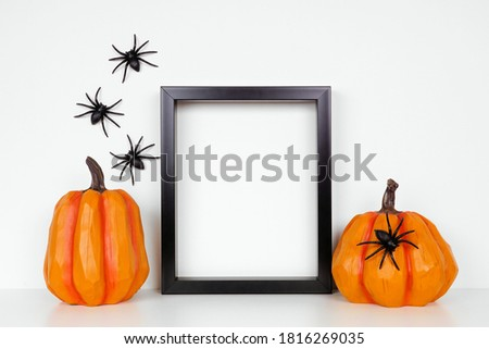 Mock up black frame with pumpkin decor on a shelf or desk. Halloween concept. Portrait frame against a white wall with spiders.