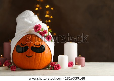 Candles and pumpkin with eye patches on brown background