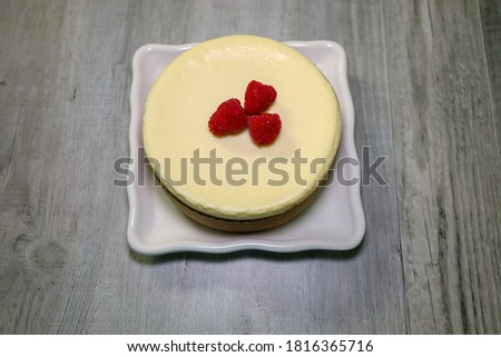 A small cheesecake with raspberries on top.