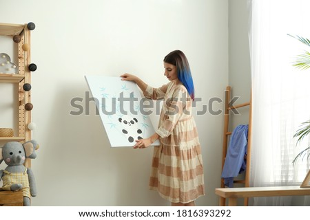Decorator hanging picture on wall. Children's room interior design