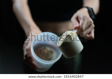 Close up of women with measuring scoop of whey protein and shaker bottle, preparing protein shake. #1816402847