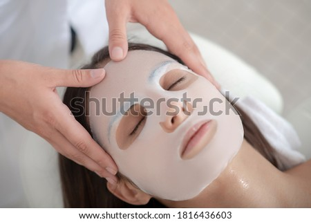 Facial mask. Cosmetologist applying facial mask sheet on womans face Royalty-Free Stock Photo #1816436603