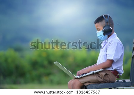 Asian elementary school-aged boys living in rural areas and schools in rural Thailand. Wear a mask to prevent the coronavirus (COVID 19) elementary school children online using a laptop to watch. #1816457567