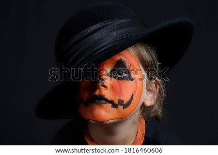 sad child with a pumpkin pattern on his face on a black background, Halloween and looks like a Joker.