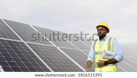 Portrait of happy solar power plant worker walking carrying rolls of paper with construction diagrams and plan.