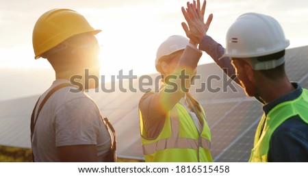 Happy employees of solar power plant raise their hands and shout for joy, clapping each other. People are satisfied with result of their work success.