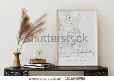 Modern scandinavian home interior with design wooden commode, mock up poster map, feather in vase, book and personal accessories in stylish home decor. Template. Royalty-Free Stock Photo #1816543985