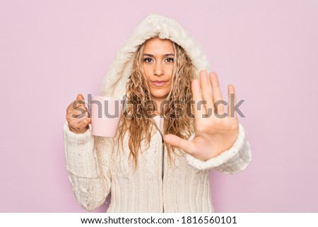 Young beautiful blonde woman wearing casual sweater with hood drinking cup of coffee with open hand doing stop sign with serious and confident expression, defense gesture #1816560101