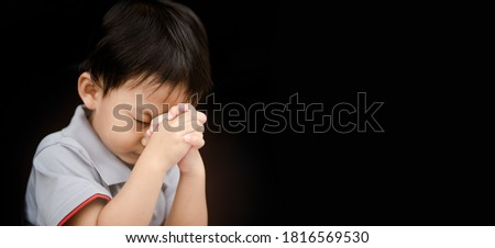 Little toddler boy keep praying for world pandemic coronavirus Covid-19 black banner background.Stay at home praying to GOD.Online church worship in sunday.Hands praying at home.Religion, Christian.
