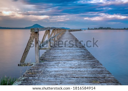 Old wooden wharf shot with long exposure during sunset. Location is Tokaanu Wharf located in Taupo region of North Island, New Zealand. #1816584914