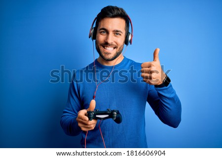 Young handsome gamer man with beard playing video game using joystick and headphones happy with big smile doing ok sign, thumb up with fingers, excellent sign