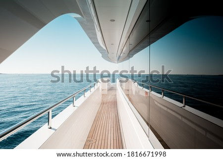 Beautiful detail of a superyacht upper deck corridor reflection on the glass windows, featuring the yacht's architectural design Royalty-Free Stock Photo #1816671998