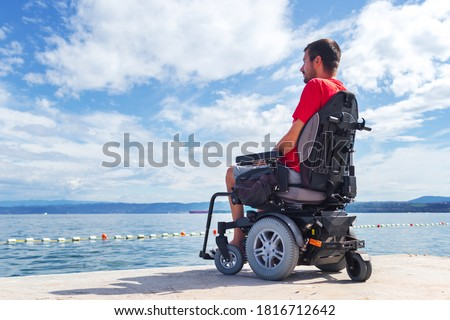Man with muscular dystrophy on electric wheelchair outdoors looking at sea. Royalty-Free Stock Photo #1816712642
