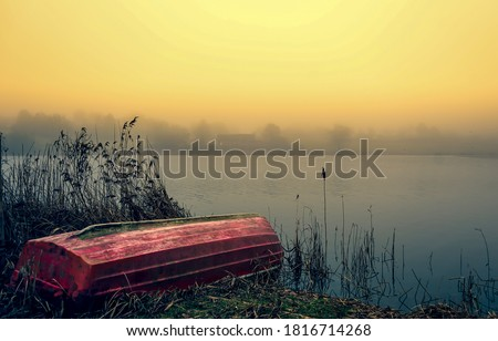 Lake boat in sunrise fog. Boat on shore in sunrise fog. Sunrise lake boat view. Lake boat sunrise scene #1816714268