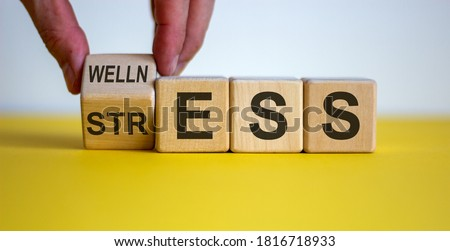 Wellness instead of stress. Hand turns a cube and changes the word 'stress' to 'wellness'. Beautiful yellow table, white background. Concept. Copy space. Royalty-Free Stock Photo #1816718933