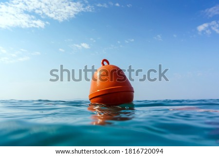 Orange buoy in the waves of the Adriatic Sea. Human life saving concept, SOS, water rescue. Selective focus, summer day. Makarska, Croatia, Europe. Royalty-Free Stock Photo #1816720094