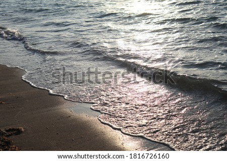 sea waves crashing on the shore at sunset