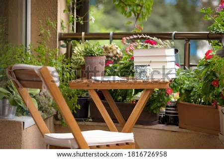 Morning coffee with relaxation on the balcony. Beautiful city terrace with many pots and vintage accessories. Royalty-Free Stock Photo #1816726958