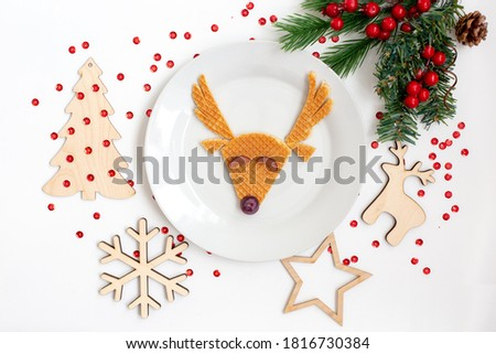 Funny Christmas children's dish of waffles and grapes with a picture of a deer on a white plate, a white table with a sprig of fir and New Year's wooden toys snowflake, fir, deer, star and sparkles.