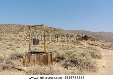 Former gold-mining town and State Historic Park in California's Bodie Hills, near the Nevada border. Old well in the center of the ghost town. Royalty-Free Stock Photo #1816753352